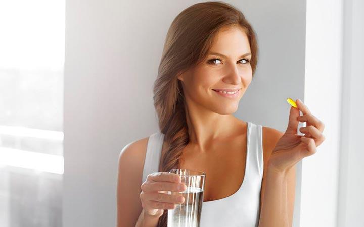 Женщина принимает таблетки