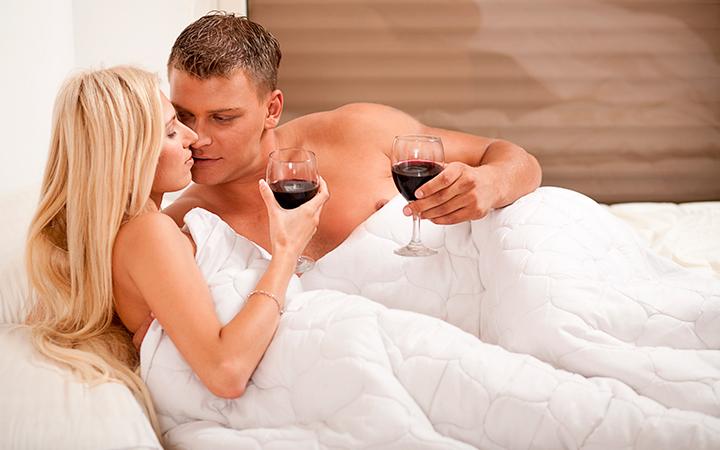 Мужчина и женщина пьют вино в постели